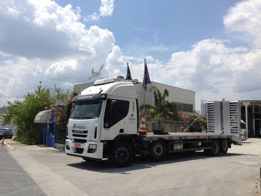 Caixa de carga útil de 8.90m de comprimento x 2.60m de largura, com capacidade máxima de carga de 15000kg, piso da prancha em madeira, rampa de acesso traseiro em aço com acionamento hidráulico.